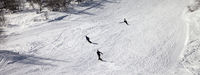 Skiers and snowboarders on ski slope at sun winter day