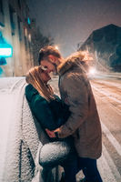 Young adult couple kissing each other on snow covered street