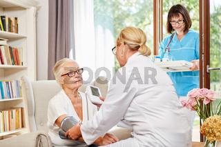 Ärztin misst den Blutdruck bei einer Seniorin