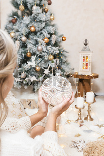 A woman holds a glittering christmas bauble for the tree