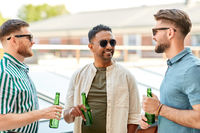 happy male friends drinking beer at rooftop party