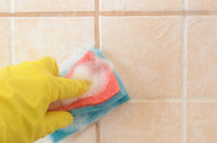 hand in yellow protective glove with sponge washes ceramic tiles with washing foam . Early spring cleaning or regular clean up.Space for text in the right.
