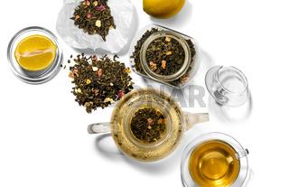 Tea, teapot, spoon and lemon on a white background