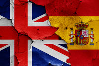 flags of UK and Spain painted on cracked wall