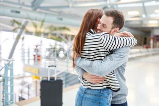 Junges Paar umarmt sich beim Wiedersehen im Flughafen