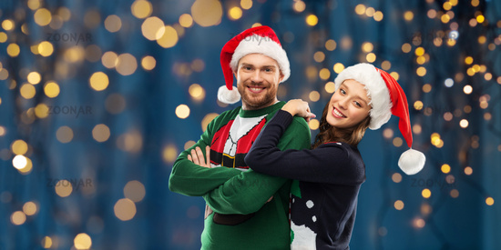 happy couple in christmas sweaters and santa hats