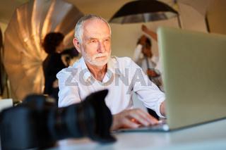 Älterer Fotograf am Laptop Computer  im Fotostudio