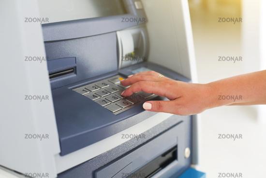 Young tourist woman using banking machine