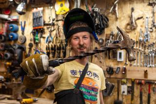 Metalworker holding hammer in workshop