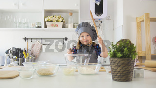 Portrait of little girl baker on kitchen