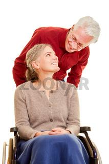 Mann betreut Seniorin im Rollstuhl bei Altenpflege
