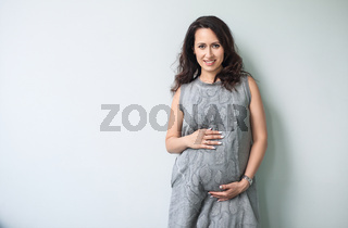 Pregnant woman touching her belly with hands