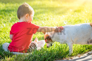 Cute Baby Boy Sitting In Grass Petting Dog