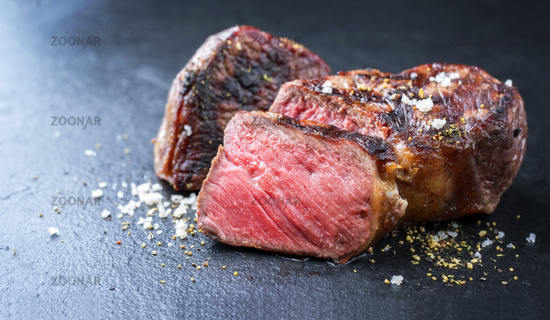 Barbecue wagyu roast beef sliced as top view on a metal board with copy space left
