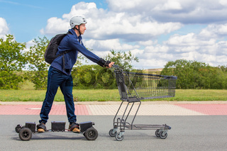 Boy on mountainboard pushing shopping cart outside