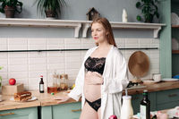 Beautiful young pregnant woman in black lace lingerie and white robe eating breakfast.