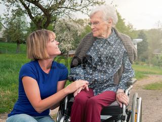 Seniorin im Rollstuhl mit junger Pflegekraft