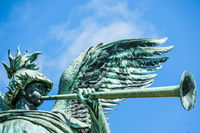 Angel statue playing the trumpet in front of blue sky