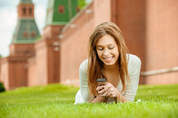young beautiful woman laughing lies on a green lawn with Mobile Phone