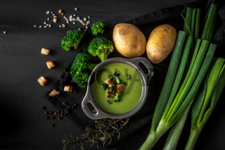 Spring detox broccoli green cream soup with potatoes and vegan cream in bowl on dark wooden board over black background, top view. Clean eating, dieting, vegan, vegetarian, healthy food concept