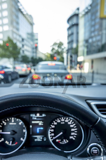 Concept shot of traffic jam in the city with close-up of steering wheel and blurred cockpit and streets with car during slowing down