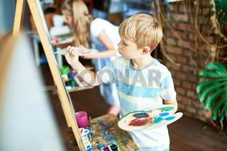 Cute Boy Painting in Art Class