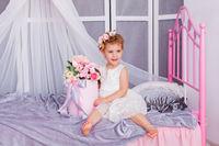 Baby girl sitting on her bed wearing headband
