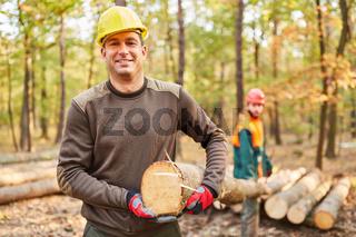 Zwei Holzfäller tragen einen Baumstamm