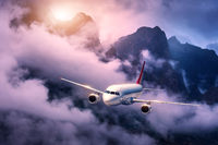 White aircraft is flying in purple clouds against high mountains