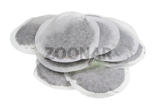 Round paper bags with dry green tea heap isolated macro