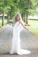 Full length portrait of beautiful sensual young blond bride in long white wedding dress and veil, holding bouquet outdoors in natural background