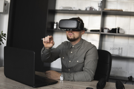 Young bearded man sitting against computer with virtual reality glasses trying to touch something or tap some thing in front of what he seeing. Modern technologies. The concept of future technology.
