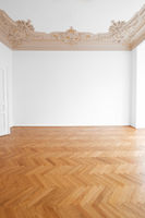 parquet floor , white walls and stucco ceiling in empty room after renovation -