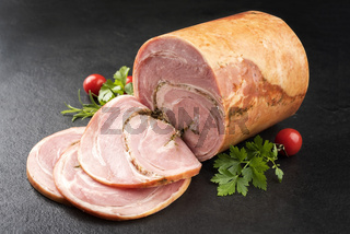 Traditional Allgauer veal roast roll sausage sliced and as piece with tomatoes and chili as closeup on a slate slab