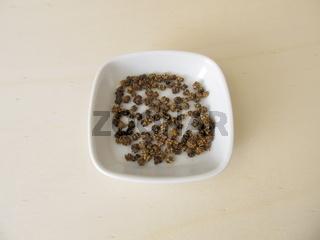 Mangoldsamen, Samen vom Mangold auf einem Holzbrett
