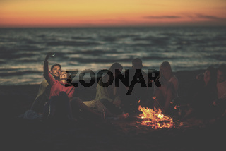 a group of friends enjoying bonfire on beach