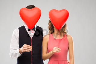couple hiding behind red heart shaped balloons