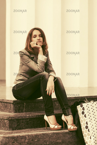 Sad young fashion woman in grey blazer and dark blue jeans sitting on steps