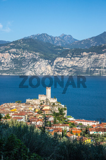 Idyllic coastline in Italy: Blue water and a cute village at lago di garda, Malcesine, sunset