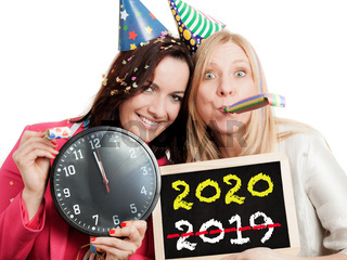 Two women holding a chalkboard and a clock isolated on white background. New year 2020 concept.