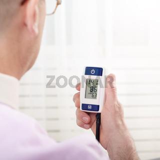 Man read measurement result from digital blood pressure monitor