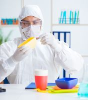 Chemist checking and testing plastic dishes