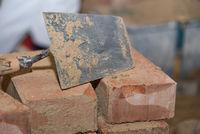 Maurerkelle und kleine Ziegelsteine - Nahaufnahme Glättekelle