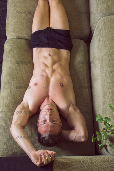 Topless naked young man resting on sofa