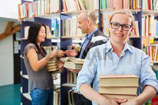 Frau als Buchhändler mit einem Stapel Bücher