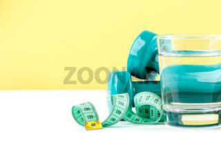 Dumbbells, centimeter and a glass of water on a white-green background.