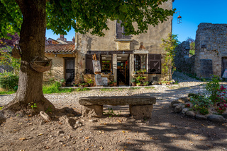 Old fashioned store with weathered stone bench, Perouges, France