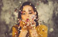 Happy beautiful brunette girl wearing yellow sweater blowing on confetti
