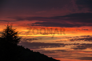 Sunset with burning red and yellow sky and shadows of tree and hill