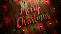Merry Christmas text and colorful garland on wood background